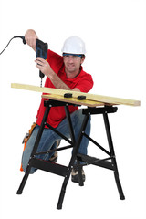 Man drilling through plank of wood