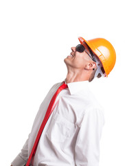 Businessman in glasses and construction helmet looking up