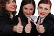 Three corporate women giving the thumbs-up