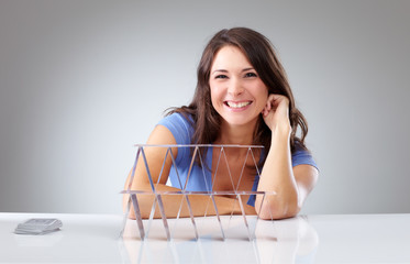 Smiling young woman with a house of cards