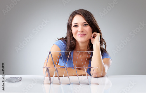 Proudly young woman with a house of cards