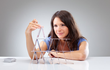 Young woman is making a house of cards 2