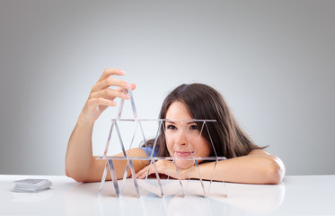 Young woman is making a house of cards 1
