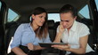 Successful business couple with tablet computer in the car