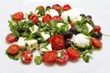 Insalata con rucola, feta, olive nere, mozzarella e pomodorini