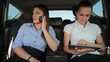 Two businesswomen with tablet computer and mobile phone in car