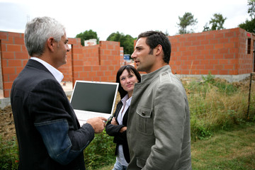 Couple and agent looking at a new-build holding a laptop