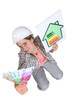 Tradeswoman holding up cash and an energy chart