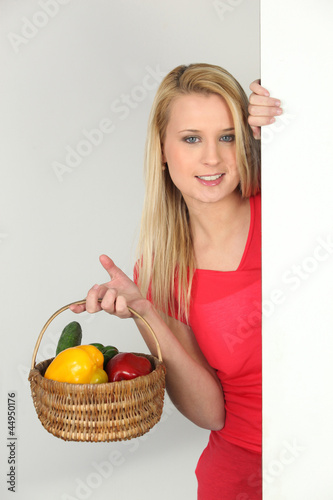 Teenage girl with basket of vegetables
