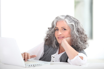 mature grey-haired lady with laptop