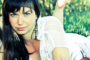Frau mit Sommersprossen in einer Wiese liegend