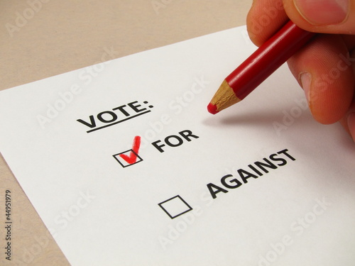 Voting 'yes' on a paper ballot with a red pencil