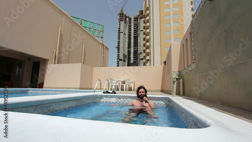 man in swimming pool at roof of apartment in Bahrain