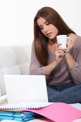 Young woman checking her emails while drinking a cup of tea