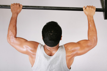 Reaching Goal: Strong man doing pull-ups on a bar in a gym