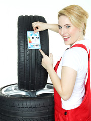 Female car mechanic showcases tire label on white background