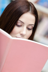 Female student reads the book at the library. Information