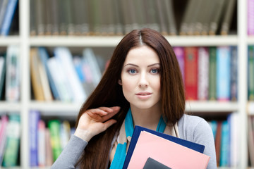 Female student with books at the library. Research. Information