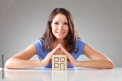Young smiling woman make a roof with hands, symbolical