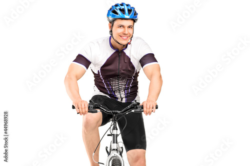 A male bicyclist posing on a bicycle