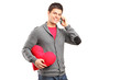 Male holding a red heart shaped pillow and talking on a phone