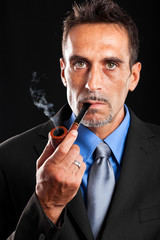 Fashion portrait of a businessman smoking a tobacco pipe