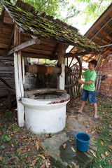 Schoolboy getting water from well