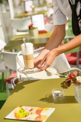 Waitress hands close up serving latte cafe
