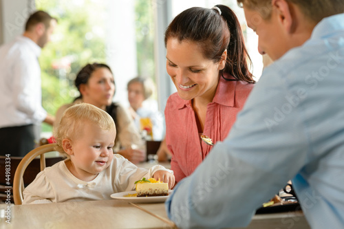 Mother and father with child eating cake