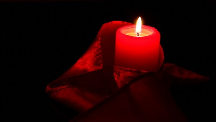 Silk and red candle on black background.