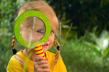 девочка смотрит через лупу