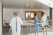 Woman walking through a hospital holding a drip