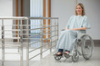 Smiling woman sitting in wheelchair in hospital corridor