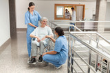Two nurses talking with  old women sitting in wheelchair