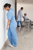 Distressed nurse standing against wall