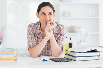 Woman looking away while holding a pen