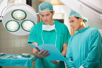 Two surgeons studying file in operating theatre