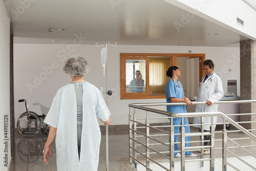 Woman walking through a hospital holding a drip