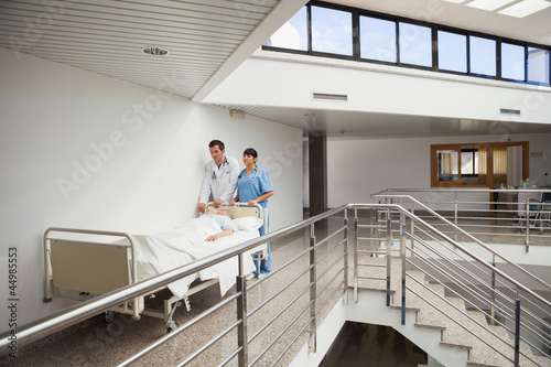 Doctor and nurse pushing patient in bed