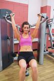 Woman using weights machine