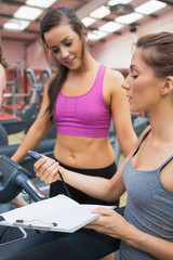 Female trainer showing client her time on treadmill