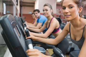 Four people smiling and riding on an exercise bike