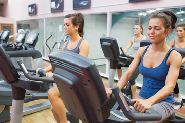 Women riding on  exercise bikes in spinning class