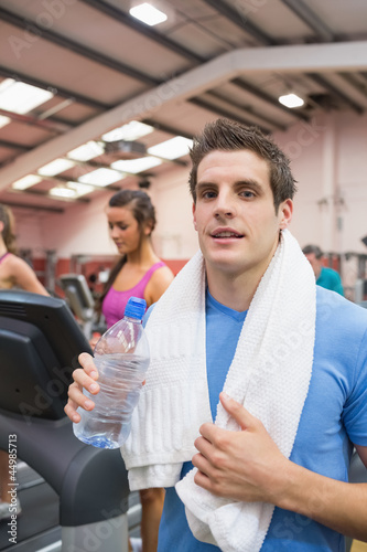 Man smiling and drinking water in gym