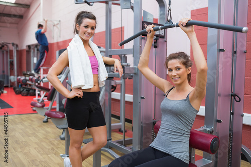 Woman stands beside friend using weights machine