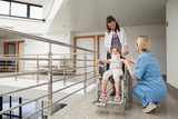 Nurse talking with child in wheelchair and neck brace with mothe