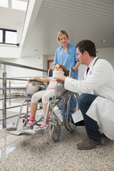 Doctor crouching next to child in wheelchair with nurse pushing
