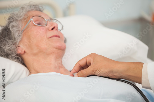 Doctor using stethoscope on elderly patient