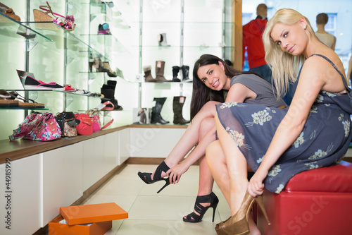 Women trying on shoes smiling