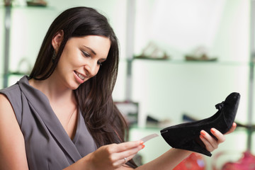 Woman looking at price tag of shoe and smiling
